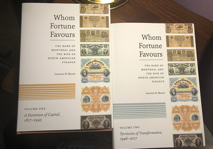 Whom Fortune Favours books, volume 1 & 2 sitting on a table