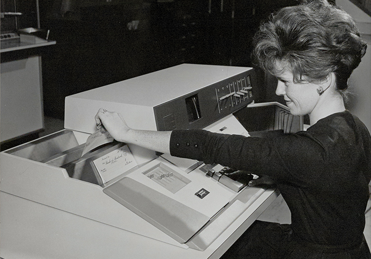 Women feeding cheques into printer